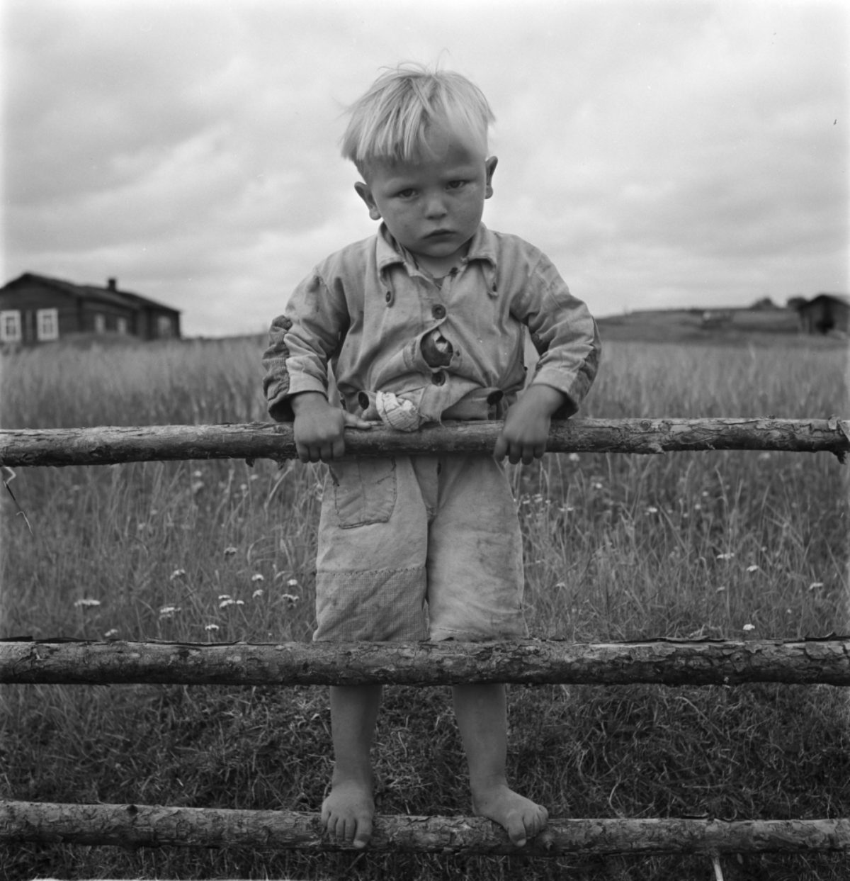 A boy who came to see a bus, standing on a fence in Suomussalmi in 1939.​ Photo: Uuno Peltoniemi / Picture Collections of the Finnish Heritage Agency