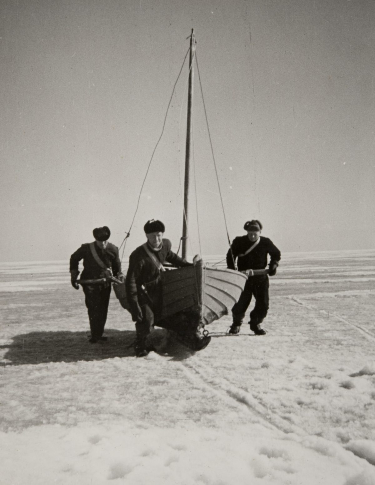 Seal hunters pulling their boat across ice in the Gulf of Finland, off the shores of Haapasaari. Photo: Jorma Jussilainen / Picture Collections of the Finnish Heritage Agency