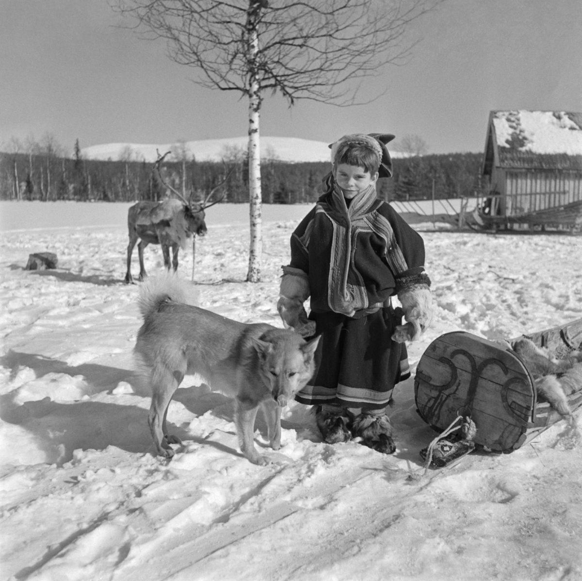 Markku Kurkkio poseeraa UA Saariselle liian suuressa lapinpuvussa ja liian pienessä neljän tuulen hatussa 1954. Kuva: UA Saarinen / JOKA / Museovirasto