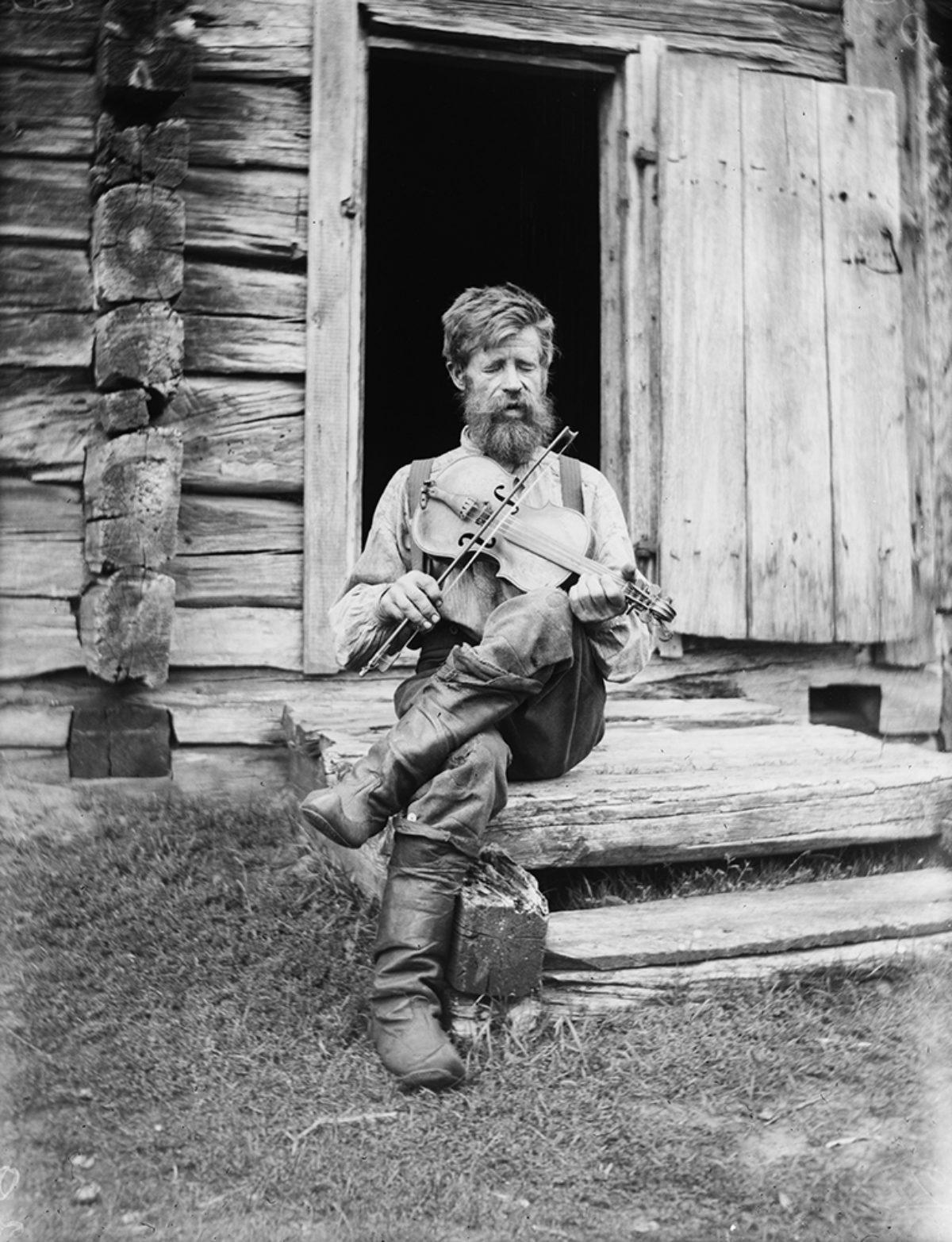 Kyrölä soittaa viulua. Hailuoto, 1912. Kuva: Samuli Paulaharju / Museoviraston Kuvakokoelmat