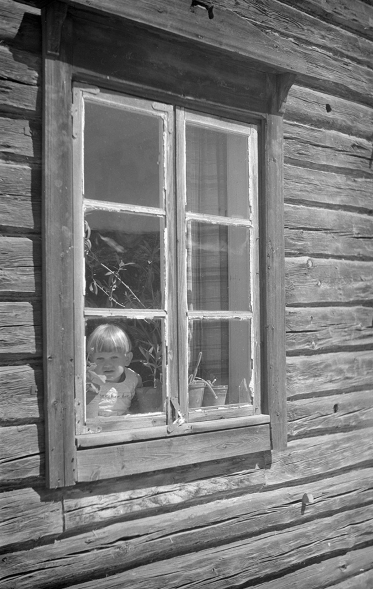 A child in a window in Hartola. Photo: Matti Poutvaara / Picture Collections of the Finnish Heritage Agency