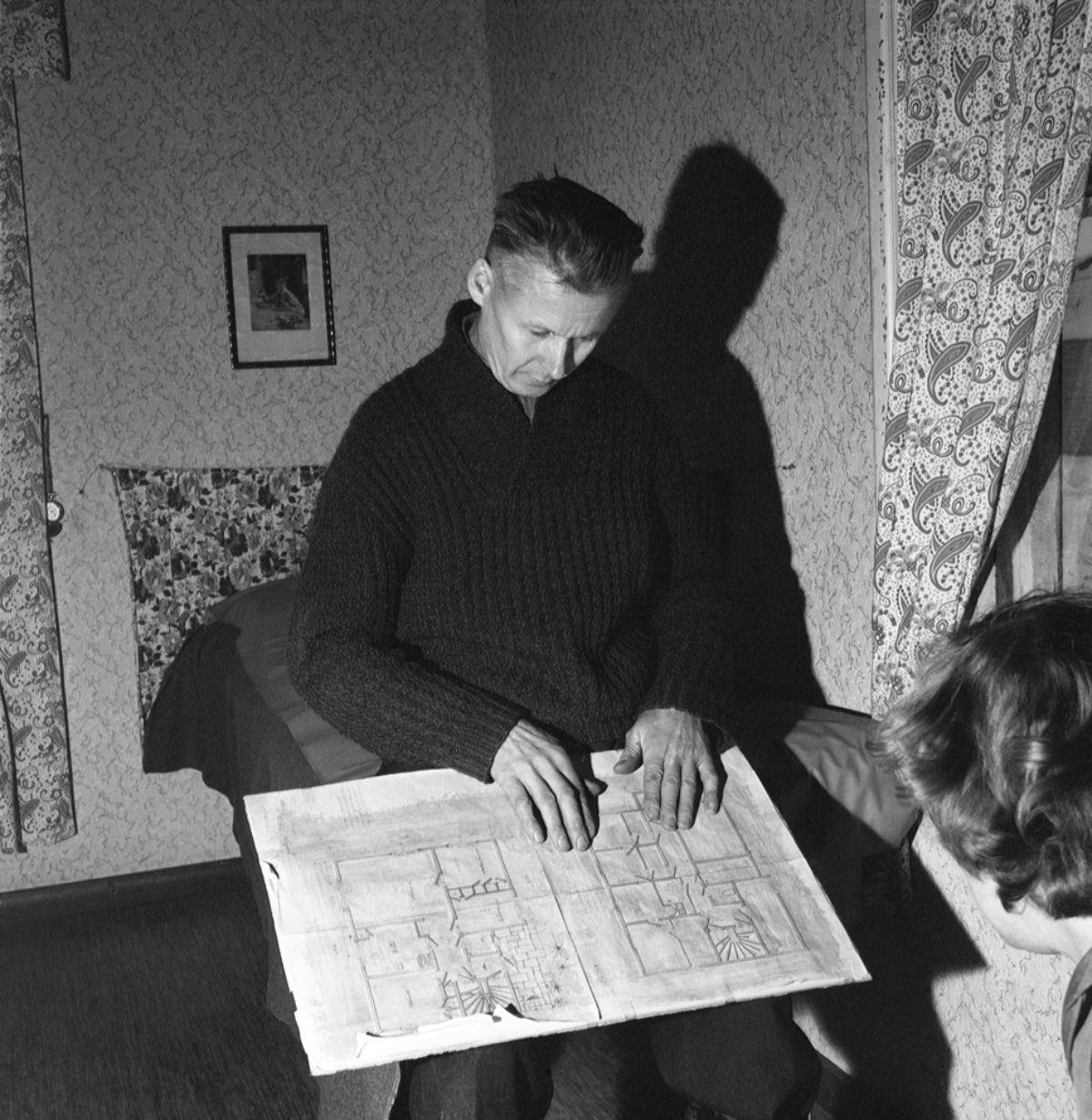Johan Venninen tutkii talonsa rakennuspiirustuksia Hyvinkäällä 1959. Kuva UA Saarinen / JOKA / Museovirasto
