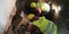 Johanna Roiha-takana ja Aleksander Suvorov etualalla kaivavat esiin perustuksia tulli- ja pakkahuoneen lattian alta.. Kuvaaja: John Lagerstedt, Museovirasto